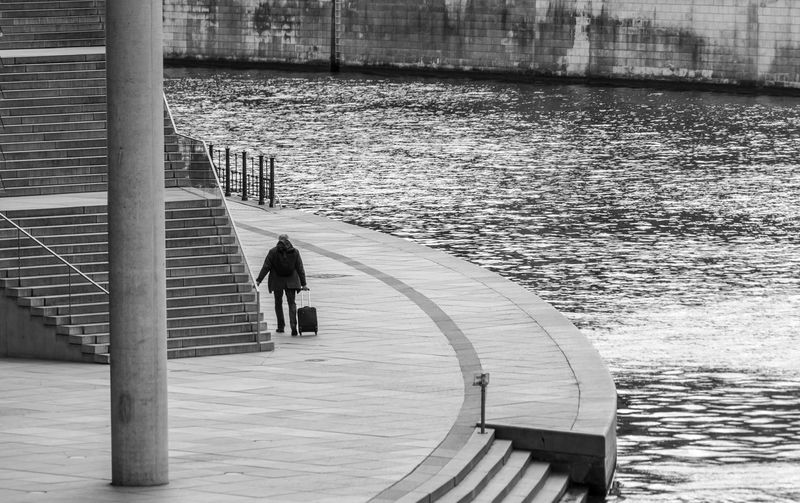 Black And White Street Photography City River Spree Government District Downtown District Traveling Bag Modern Water One Person Real People Architecture Rear View Built Structure Day Railing Lifestyles Nature Full Length Men Transportation Leisure Activity Outdoors Nautical Vessel Standing Staircase