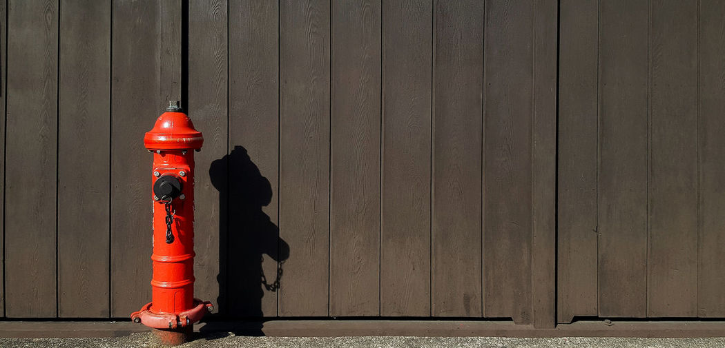 Red fire hydrant on footpath against wall