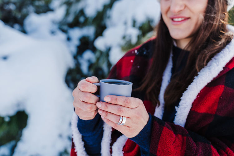 Close-up of woman holding coffee cup during winter
