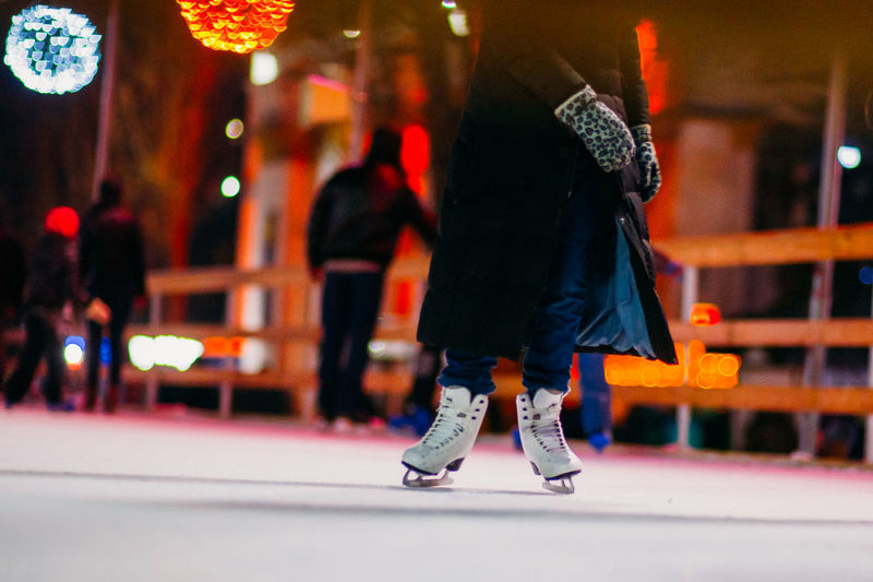 Low section of person ice-skating during christmas at night