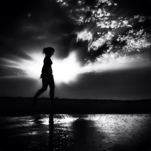 Silhouette of woman standing by sea against cloudy sky