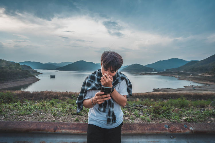 Man photographing while using mobile phone by lake against sky