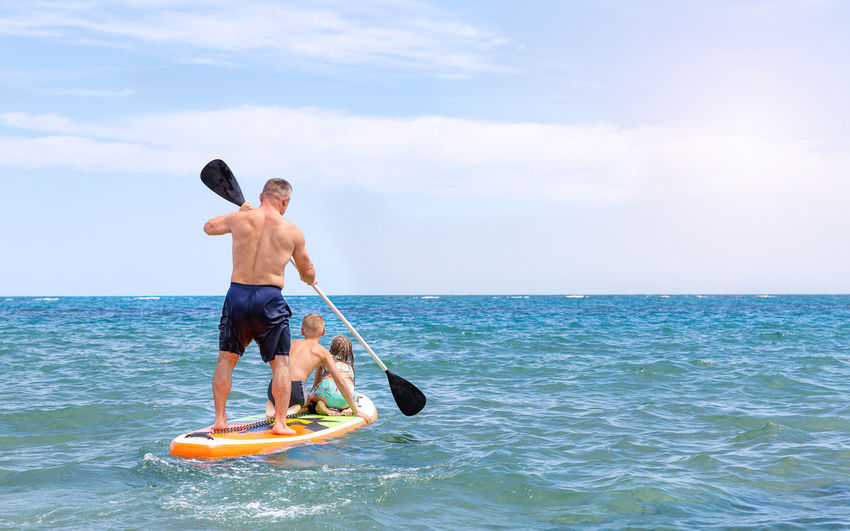 A father and two children ride a sup board on the sea, sail towards the horizon. paddleboarding.