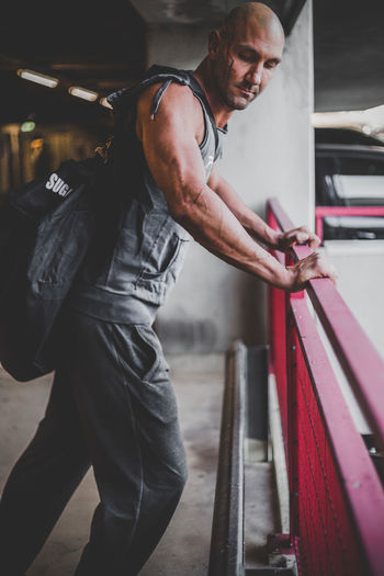 Side view of muscular man leaning on railing