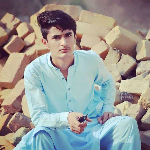 Portrait of serious young man wearing kurta while sitting on rocks