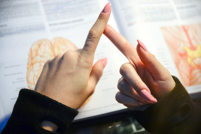 Cropped image of woman touching fingers against book