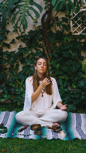 Full length of young woman meditating while sitting outdoors