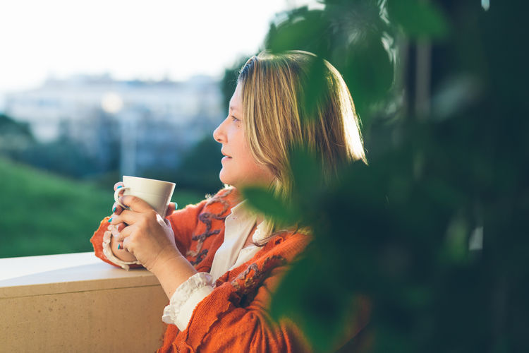 Adult Beautiful Woman Blond Hair Close-up Coffee - Drink Coffee Cup Day Drink Drinking Focus On Foreground Food And Drink Freshness Holding Lifestyles Nature One Person One Young Woman Only Outdoors People Real People Side View Tree Women Young Adult Young Women