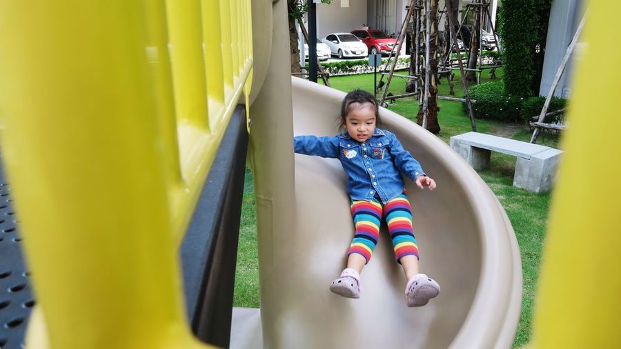 Full length of cute happy asian girl on slide at playground