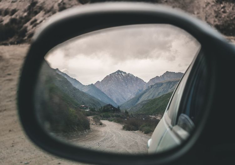 Reflection of mountains in side-view mirror