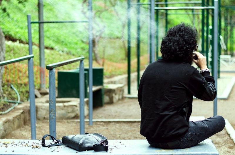 Rear view of man smoking outdoors