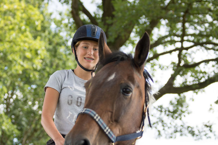 Low angle view of happy teenager riding horse