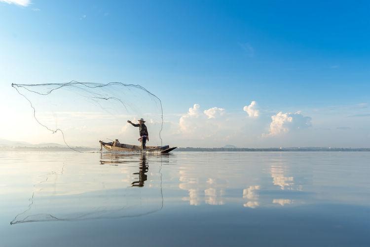 Man on boat fishing in lake against sky