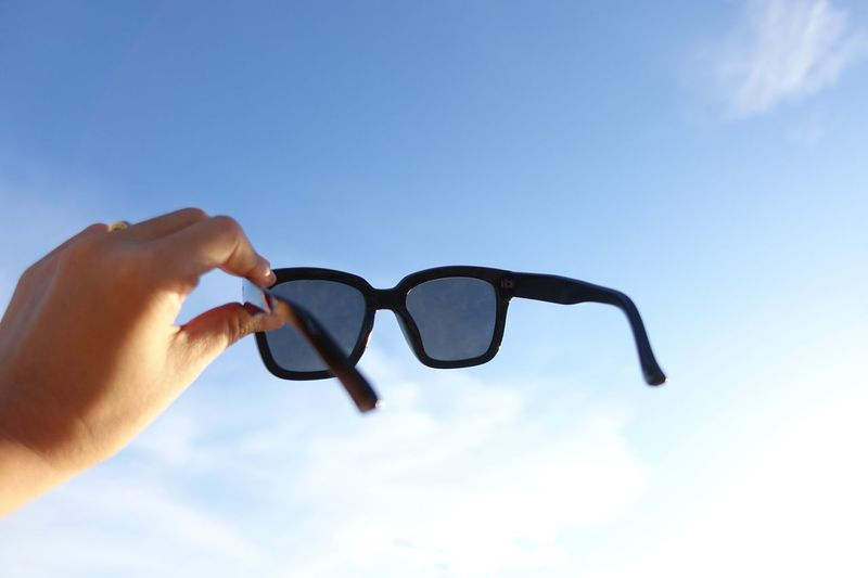 Midsection of man holding sunglasses against blue sky