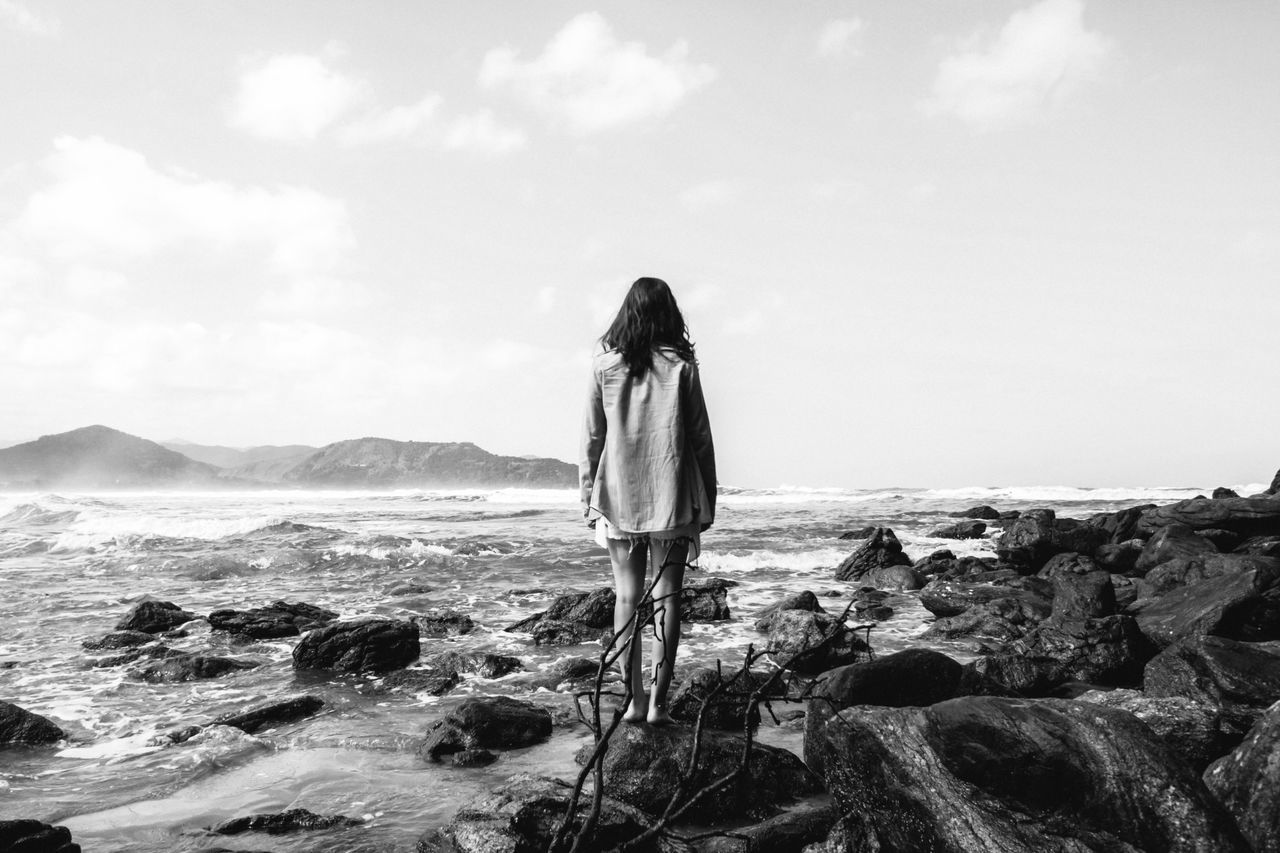 Woman standing on rocky beach