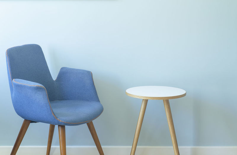 Close-up of empty chairs on table against wall