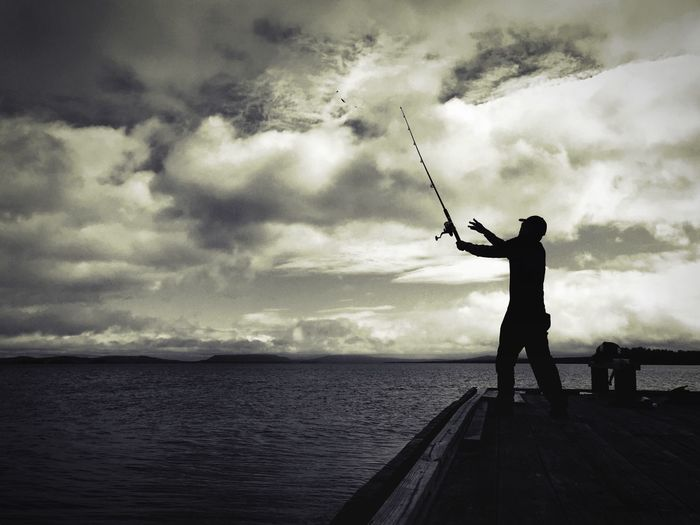 Side view of silhouette man fishing at calm sea