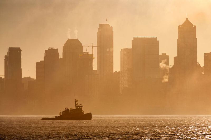 Seattle Sunrise. A tugboat plies the waters of Elliott Bay along the Seattle waterfront on a foggy summer morning. Elliott Bay Morning Pacific Northwest  Puget Sound Seattle Washington Architecture City Cityscape Dawn Fog Foggy Modern Nautical Vessel No People Outdoors Sea Skyscraper Sunrise Tower Tugboat Urban Urban Skyline Water Waterfront