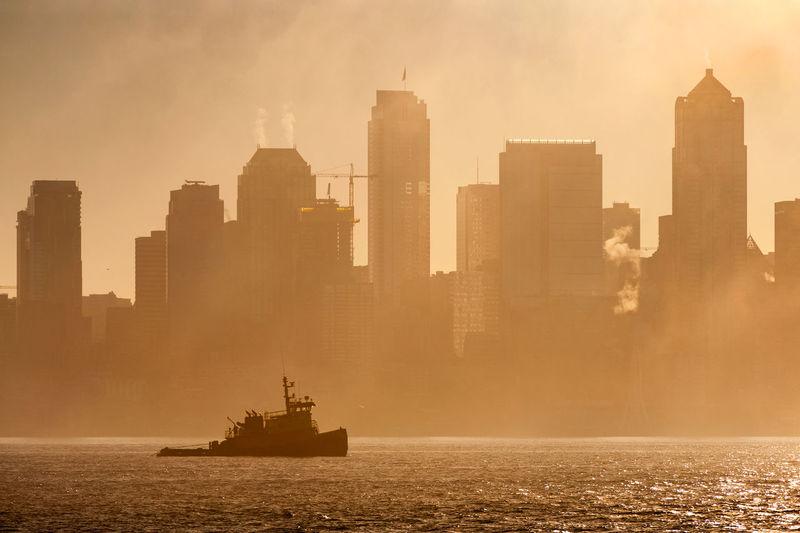 Tug Boat On Elliott Bay Against Buildings In City During Foggy Weather