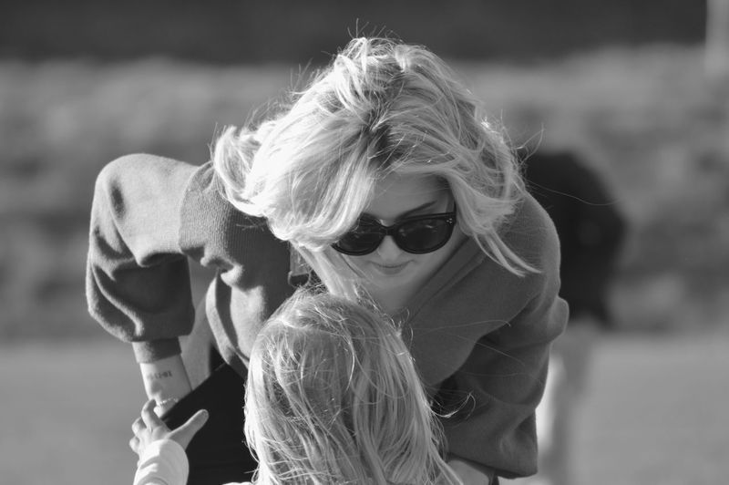 Mother wearing sunglasses while looking at daughter