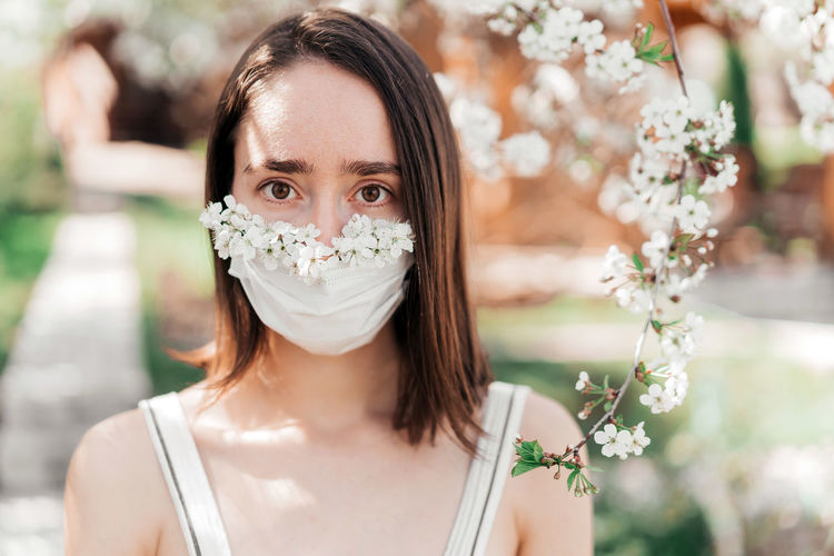 Portrait of sad young woman in protective medical face mask with flowers near blooming tree.