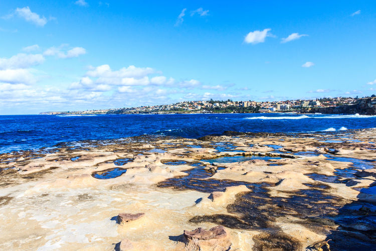 Person walking along deserted beach on a beautiful sunny day, Freshwater,Sydney,New South Wales, NSW, Australia Clovelly  Coogee Looking Out To Sea Shark Point Australia Beautiful Blue Sky Clouds Coast Coastal New South Wales  Ocean Rock Pools Rocks Sunny Nature