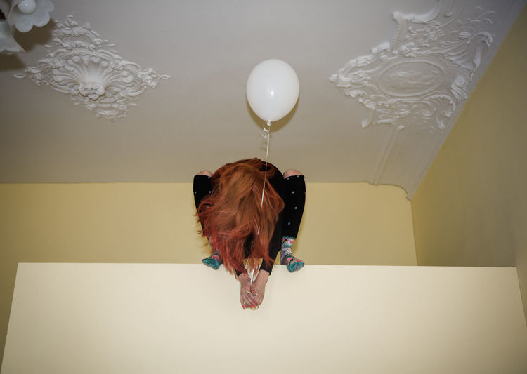 Portrait of dog with balloons against wall