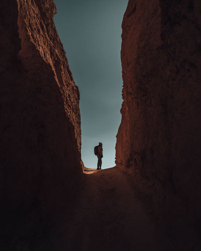 Mid Distance Of Woman Standing Amidst Rock Formation During Sunset