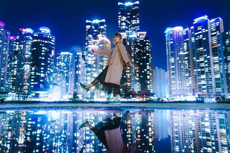 Portrait of woman standing by lake against illuminated buildings in city at night