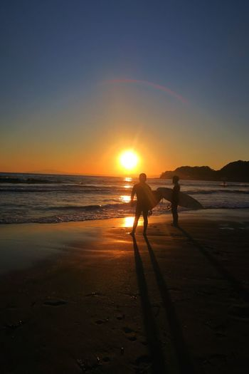 Two silhouette people with surfboards on beach at sunset