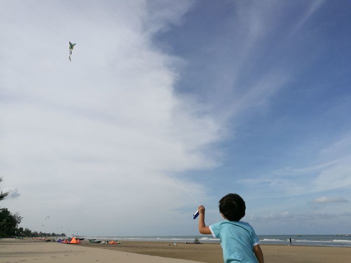Rear view of boy flying kite while standing on sand at beach