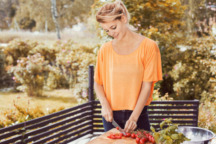 Woman holding food outdoors