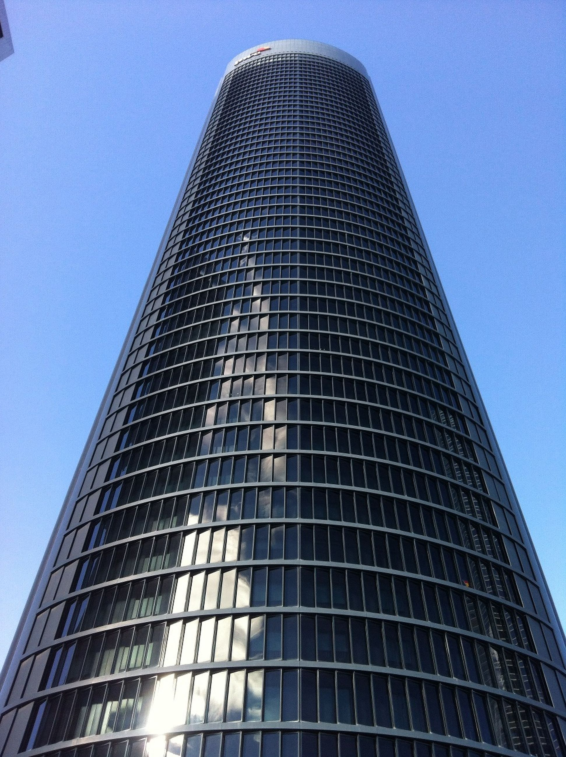 low angle view, architecture, building exterior, modern, built structure, skyscraper, tall - high, office building, tower, city, clear sky, glass - material, building, blue, tall, reflection, day, outdoors, no people, sky