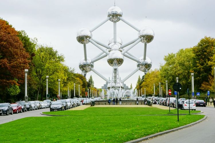 Atomium By Fountain Against Cloudy Sky