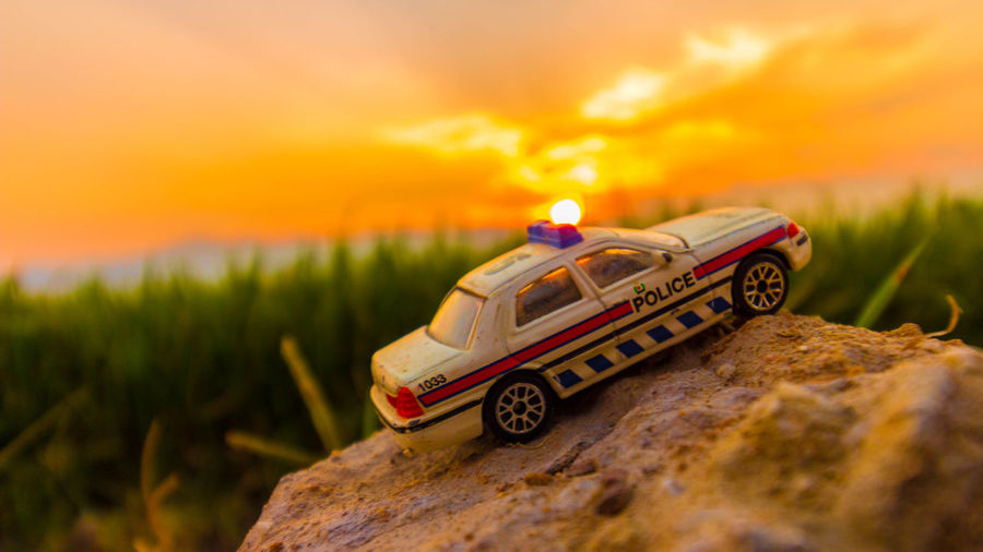 Close-up of car on land against sky during sunset