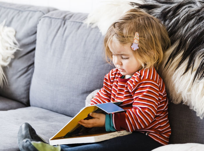 Girl with book sitting on sofa at home