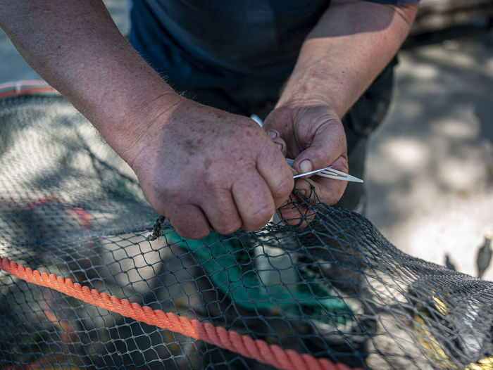 Close-up of man working with fishing net