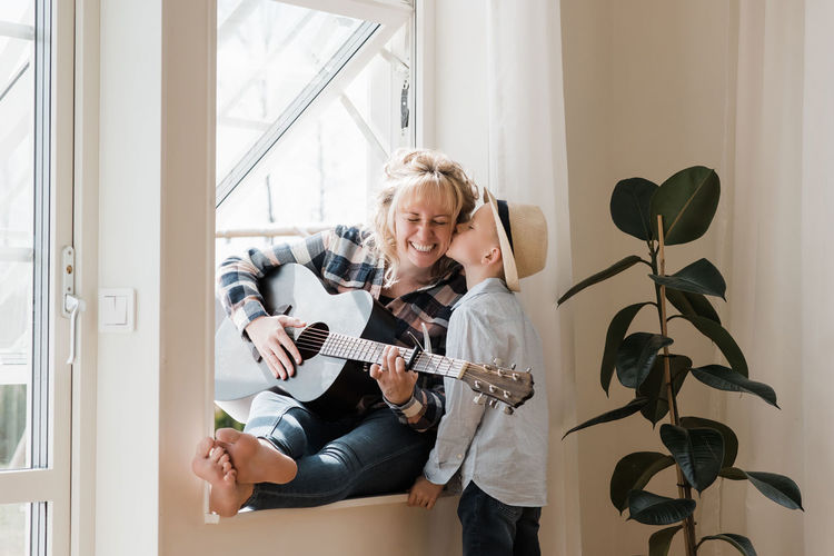 Young woman playing guitar at window