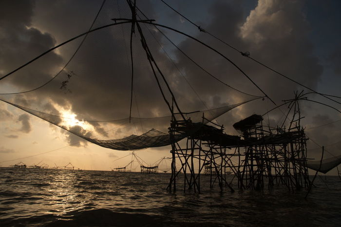 Silhouette of Large traditional Thai definition on a lake in Thailand. Asian  Dawn Light Fishing Net Kind Of Fish-trap Mesh Square Dip Net Sunset Silhouettes Thai Definition Thailand Beauty In Nature Cloud - Sky Clouds And Sky Group Of Objects Lake Nature Net Outdoors Scenic View Scenics Sky Sunset Traditional Twilight Sky Water Wooden