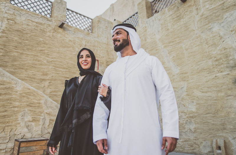 Low angle view of smiling couple standing against wall in town