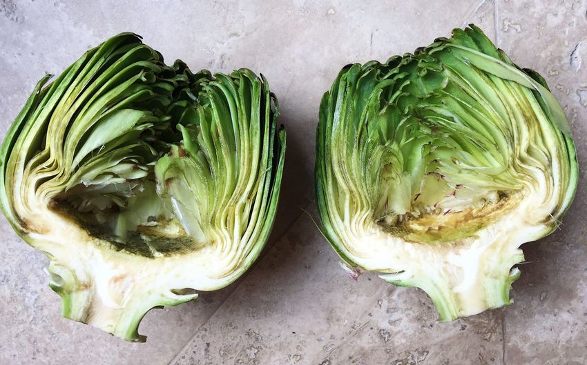 High Angle View Of Halved Artichoke On Table