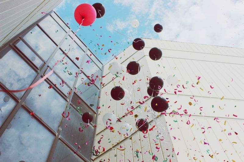 Low Angle View Of Balloons And Confetti In Mid-Air By Building