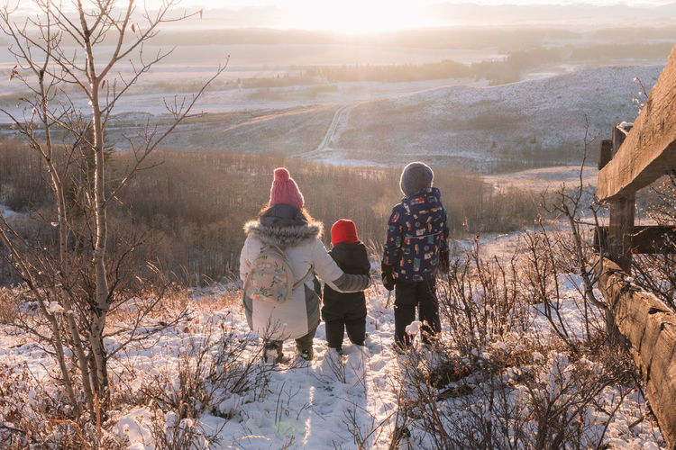 Scenic view of a mom and her children looking at the snowy landscape at sunset