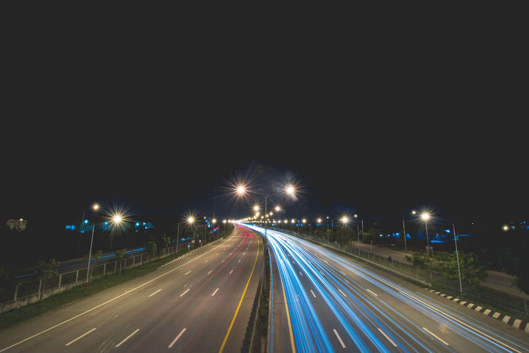 Architecture City Diminishing Perspective Direction Highway Illuminated Light Trail Long Exposure Mode Of Transportation Motion Multiple Lane Highway Night No People Outdoors Road Sign Sky Speed Street Street Light The Way Forward Traffic Transportation Vehicle Light