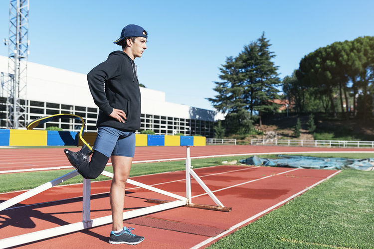 Side view of young athlete with prosthetic leg standing by railing on running track