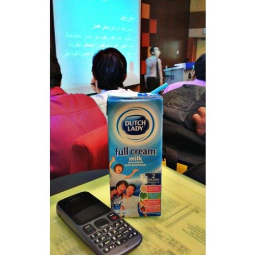 having a pack of DutchLady Fullcream Milk . my friend is presenting about ta'min ( Insurans ) nokia tamhidi dkp2 UHT recombined milk protein nutrient natural godness