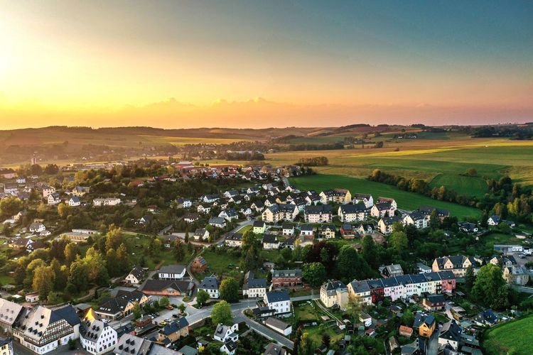 Aerial view of a small town in saxony during sunset Village Landscape Nature Saxony Hartenstein Flower Head Flower Sunset Rural Scene Agriculture Field Sunlight Hill Sky Landscape Farmland Patchwork Landscape Oilseed Rape In Bloom Blooming Plant Life Rolling Landscape Farm