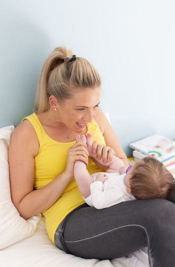 Mother Playing With Newborn Girl On Bed At Home