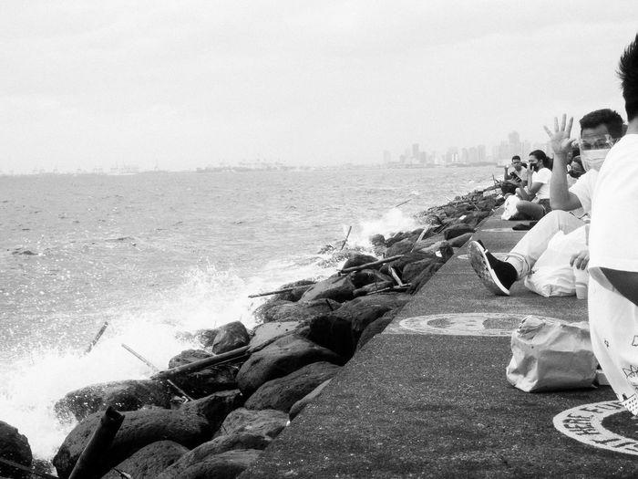 People sitting on rock by sea against sky