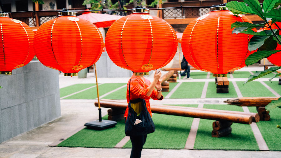 Low section of woman standing on red lanterns